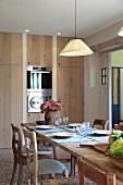 Gedecke auf Holztisch mit schlichter Hängelampe vor modernem Einbauschrank und integrierten Küchengeräten