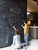 Children drawing on floor-to-ceiling blackboard partition next to kitchen