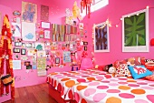 Girl's bedroom with pink walls, twin beds, colourful items decorating walls and fairy lights