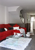 Acrylic glass coffee table in front of red upholstered sofa in open-plan designer apartment with staircase
