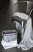 White crochet blanket on metal chair, open basket and books on floor