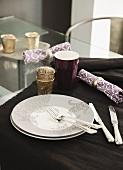 Plate, cutlery, napkin, beaker and tealight holder on table runner