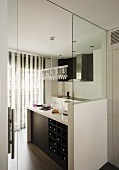 View through open door into black and white designer kitchen with pendant lamp decorated with glass beads