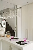 Pendant lamp with glass bead ornaments above angled base unit in designer kitchen