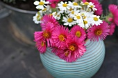 Asters and chamomile in round vase