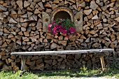 Stacked firewood with bench and decorative petunias