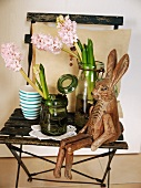 Wooden hare figurine next to glass jars of flowers on rustic folding chair