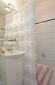 Badezimmer mit Duschvorhang an der Badewanne