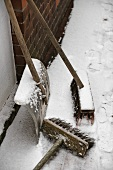 Two brooms and snow shovel at house wall