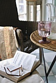 Book and eyeglasses on chair next to table with glass of water