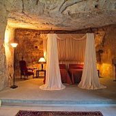 Open-plan sleeping area on platform - twin beds with canopy and lit table lamps in grotto-style niche