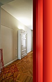 View of red wire-framed chair and herringbone parquet in grand hallway though doorway next to red wall