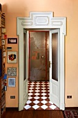 Open interior door with carved white wooden frame in apricot wall and view into foyer with chequered floor
