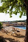 Sonniger Platz mit Tisch und Stühlen auf Kiesboden vor Pool in mediterraner Landschaft