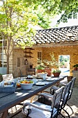Long breakfast table in sunny courtyard of Mediterranean country house