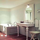 Vintage bathroom: washstand with ceramic legs next to wood-clad bathtub against mosaic-tiled walls