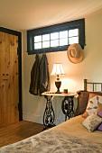 Schlichtes Schlafzimmer - Ehemaliger Nähmaschinentisch neben Bett und Wandhaken mit aufgehängter Kleidung unter Oberlicht