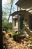 Sonniger Tag im Herbst - Herbstlaub vor überdachtem Hauseingang am Holzhaus