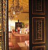Offene Flügeltür in Schwarz mit goldenen Einlegearbeiten und Blick in herrschaftlichen Salon mit asiatischem Flair