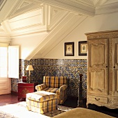 Traditional attic room with white wood panelling and comfortable upholstered armchair with matching ottoman against tiled wall
