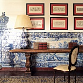 Table lamp on traditional console table against half-height blue and white tiling and framed pattern templates on wall