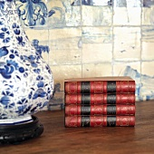 Antique books on table next to table lamp with white and blue ceramic base