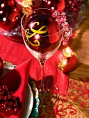 A place setting and a wine glass with red Christmas decorations