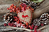 Christmas arrangement with embroidered, heart-shaped cushion