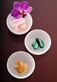 Edelsteine in Schalen mit Orchideenblüte auf farbiger Glasablage