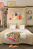 Oriental dress on double bed against wall with illuminated niche in simple bedroom
