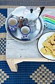 Tablett mit Espresso-Kanne und Bechern neben Teller mit marokkanischem Fladenbrot