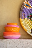 Stack of colourful plastic dishes and basketwork platter on stone shelf