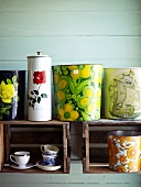 Colourful containers, planters and espresso cups in and on shelving