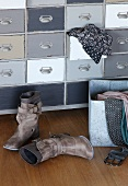 Damenstiefel auf Holzboden vor Vintage Schubladenschrank mit Kleidungsstück in offener Schublade