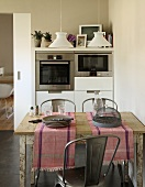 Runners and crockery on rustic kitchen table in front of modern cupboards with fitted appliances