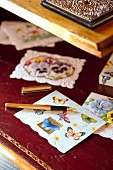 Various greetings cards with butterfly motifs and gold fountain pen on claret red leather desk blotter