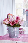 Moss wreath with bouquet of pink hyacinths and tulips in zinc bucket with heart pendant attached with washi tape