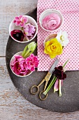 Stemless flowers in small dishes (pink primula and tulip, narcissus and white primula, dark red anemone and pink primula, pink ranunculus)