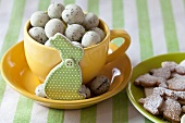 Yellow cup of quail's eggs with rabbit figure and plate of Easter biscuits