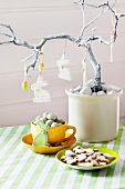 Easter arrangement with rabbits and eggs hanging from branch above cup of quail's eggs and plate of Easter biscuits