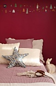 Bed decorated in cream and dusky pink with starfish cushion and rabbit ornament against wall painted dark red with row of painted miniature figures