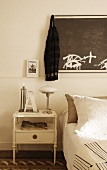 Antique bedside table with retro-style table lamp and dark artwork on wall above bed