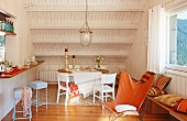 Leather butterfly chair in front of dining area with white chairs below wood-clad sloping ceiling
