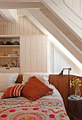 Bed with patterned bedspread in front of fitted cupboards below wood-clad sloping ceiling