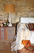 Partially visible sofa with fur blanket next to table lamp on vintage trunk against stone wall