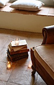 Partially visible leather armchair next to stack of books and lit tealights in front of masonry bench with cushions