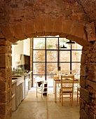 View though open stone doorway of table in front of terrace doors in kitchen-dining room