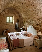 Doppelbett mit Kopfteil an Natursteinwand im Schlafzimmer mit Tonnendecke