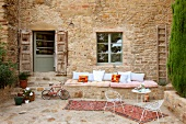 Courtyard with delicate terrace chairs and table in front of masonry bench on outside wall of Italian farmhouse
