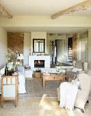 Schlichter, heller Wohnraum mit Ohrensesseln und Couchtisch vor Kaminfeuer in mediterranem Landhaus